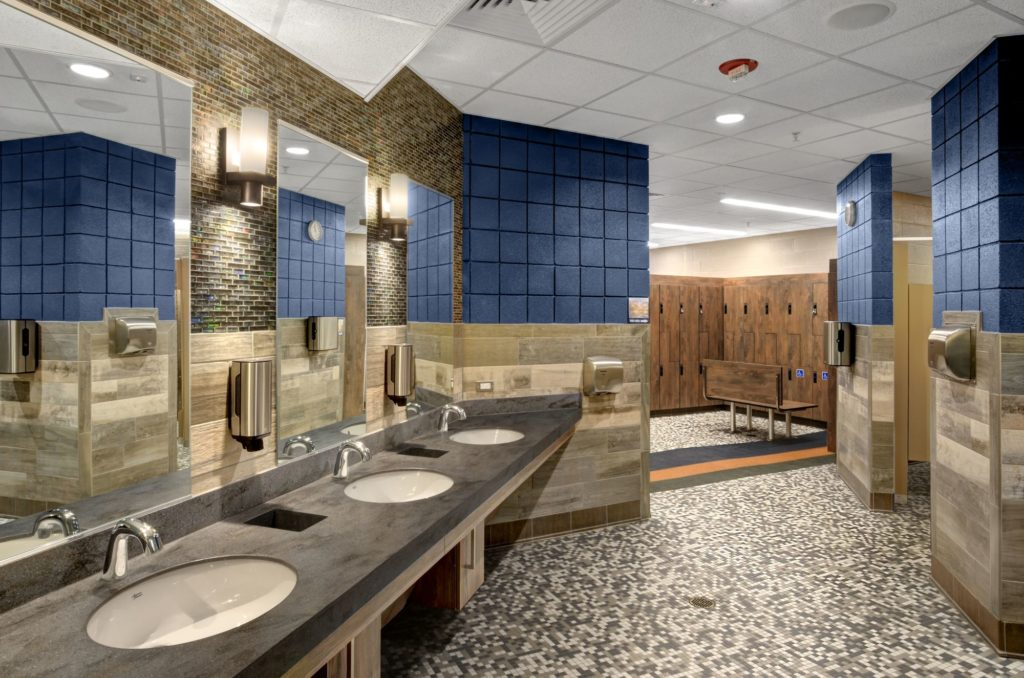 Upgraded illumination, patterned tile floor, wood tone tile wall, and wood locker all create a relaxing mountain environment at the Estes Valley Community Center in Estes Park, Colorado.